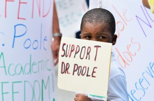 Kristopher Thurston, 4, holds a sign in front of other posters brought to show support for instructor Deandre Poole Tuesday, April 9, Thurston came to the protest with his mother and friend of Poole, Kamae Haltaufderhyde. Photo by Ryan Murphy.
